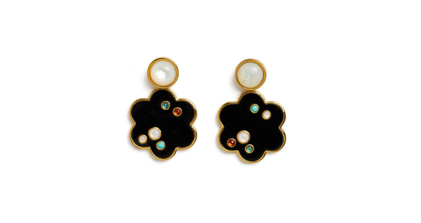 Full view of Poppy Earrings. Our charmingly stylized flower earrings have serious graphic appeal. This acrylic and gold-plated brass pair is inlaid with an artful scattering of semiprecious cabochons, and topped off by mother-of-pearl.