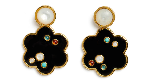 Close-up of Poppy Earrings. Our charmingly stylized flower earrings have serious graphic appeal. This acrylic and gold-plated brass pair is inlaid with an artful scattering of semiprecious cabochons, and topped off by mother-of-pearl.