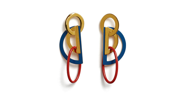 Full view of Stella Earrings In Americana. Nautical by nature. Sculptural by design. The Stella Earrings are, quite frankly, as cool as it gets. In gold-plated brass linked geometric shapes with navy and red enamel.