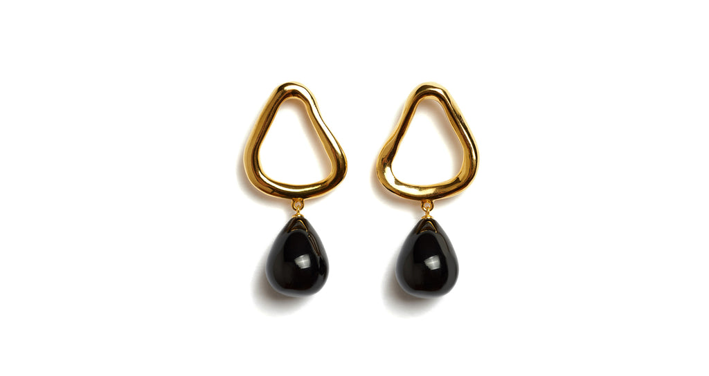 Full view of Alta Drop Earrings. Small but impactful, we love how these earrings walk the line between geometry and sculpture. With gold-plated abstract triangles and hanging black agate drops.