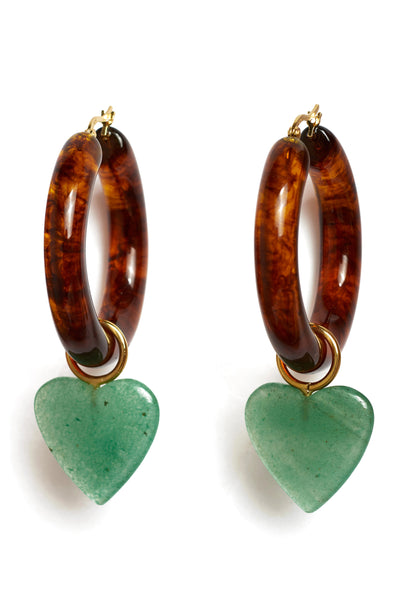 Thumbnail detail of La Playa Hoops In Tortoise. Hey, valentine. These earrings are our modern love letter to cool girls everywhere. Acrylic hoops in coveted tortoise color are punctuated with hanging green quartz heart charms.