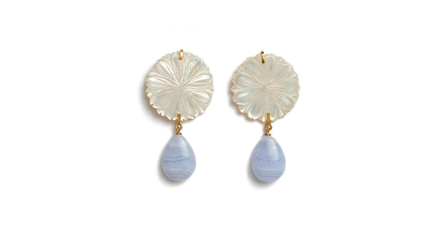 Full view of Wild Maquis Earrings. Lizzie's explorations of the uniquely fragrant hillsides of Italy was the inspiration for these beautiful hand-carved mother-of-pearl flower earrings. They feature hanging blue lace agate drops that catch the light in the most perfect way