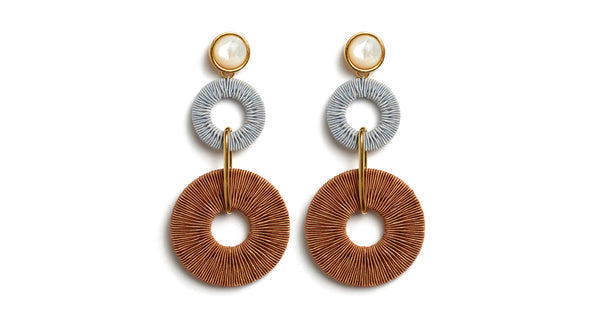 Full view of Corsica Column Earrings. Get linked in with our fashion-forward statement earrings. Pale blue and brown woven hoops are linked with mother-of-pearl tops for a fun, elevated arts & crafts vibe.