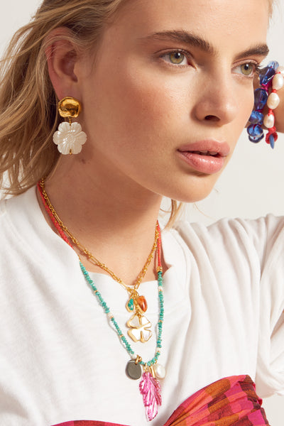 "Thumbnail of model wearing Blanc Daisy Earrings. Say it with flowers in this small but decidedly eye-catching pair. The gold-plated cast ""coin"" top earrings with hanging mother-of-pearl daisies signal spring in all its glory."