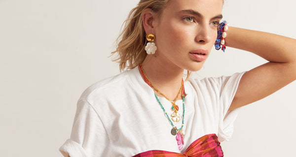 "Model wearing Blanc Daisy Earrings. Say it with flowers in this small but decidedly eye-catching pair. The gold-plated cast ""coin"" top earrings with hanging mother-of-pearl daisies signal spring in all its glory."