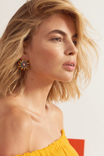 Thumbnail of model wearing Corsica Sun Earrings. Who loves the sun? Brighten any dull days in our gold-plated sunshine stud earrings, with blue and burnt orange enamel and mother-of-pearl cabochons.