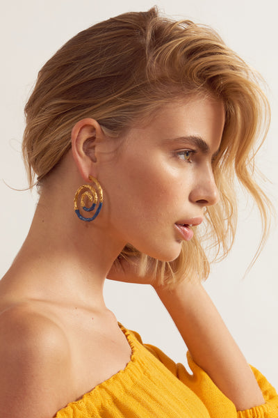 Thumbnail of model in Spiral Earrings In Navy. We can't help but be captivated by the hypnotic spiral shape and organic texture of these earrings. This version gets a nautical update with a dip in dark navy enamel.