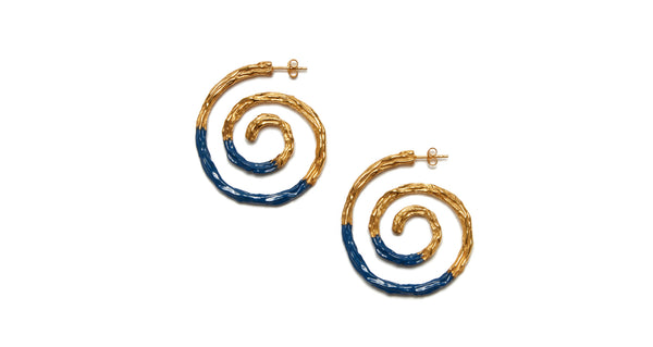 Full view of Spiral Earrings In Navy. We can't help but be captivated by the hypnotic spiral shape and organic texture of these earrings. This version gets a nautical update with a dip in dark navy enamel.