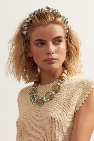 Thumbnail of model wearing Beach Hair Headband In Green. Preppy, cool, nostalgic -- this is the headband that can do it all, and that you'll want to wear all summer long. In ruched pale green and cream plaid shantung silk.