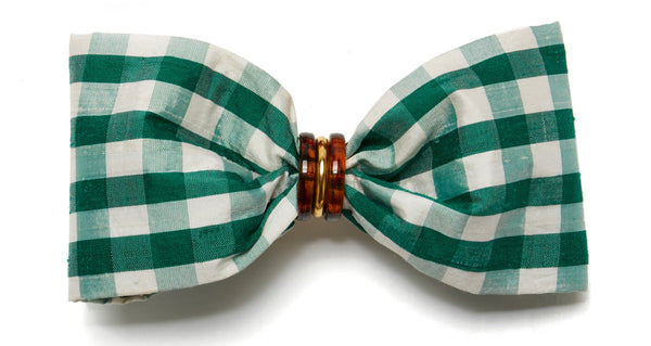 Close-up view of Good Hair Day Bow In Green. The freshest way to raise the style profile of your everyday ponytail? It's our gold-plated barrette with green gingham silk shantung bow. With tortoise and gold-plated accents.