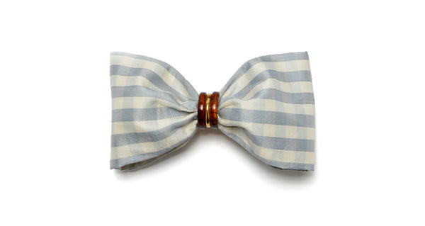 Full view of Good Hair Day Bow In Pale Blue. The easiest way to raise the style profile of your everyday ponytail? It's our gold-plated barrette with pale blue gingham silk shantung bow. With tortoise and gold-plated accents.