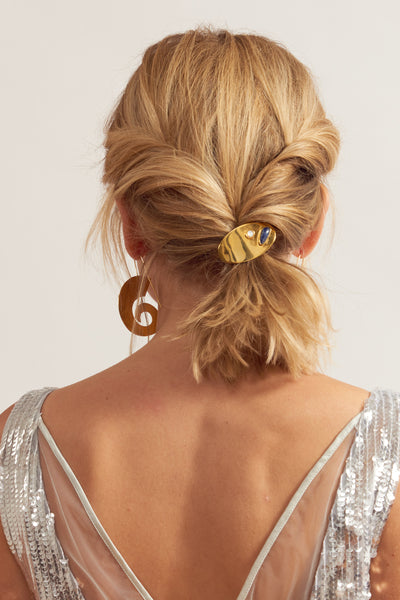 Thumbnail of model wearing  Ponytail Holder In Constellation. Sayonara, scrunchies. Bad hair days are officially banished with Lizzie's secret weapon: an achingly elegant peach-colored ponytail holder with gold-plated oval accent and mother-of-pearl and sodalite cabochon details.