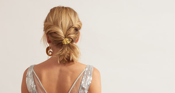 Model wearing Ponytail Holder In Constellation. Sayonara, scrunchies. Bad hair days are officially banished with Lizzie's secret weapon: an achingly elegant peach-colored ponytail holder with gold-plated oval accent and mother-of-pearl and sodalite cabochon details.