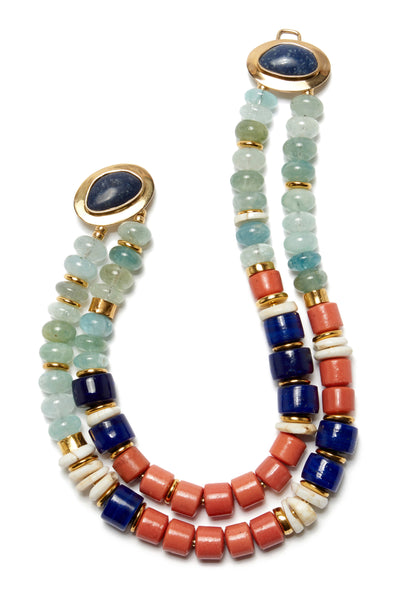 Thumbnail close-up of Ariel Necklace. The Ariel is a trove of under-the-sea-inspired sophistication. This colorful double-strand necklace is composed of blue morganite, Tibetan glass, conch shell, recycled Nigerian glass and gold-plated beads.  With gold and dumortierite stone closure that can be worn in the back, side or front.