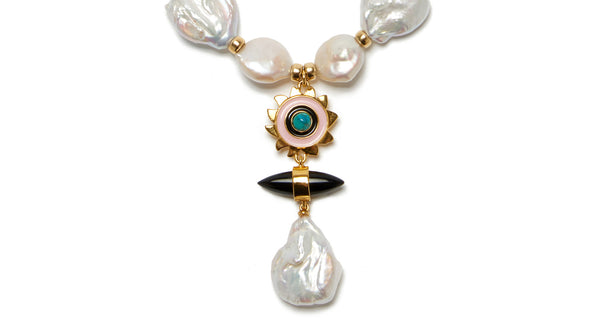 "Pendant detail of Apollo Pearl Necklace. Whether you're a beach babe or ballet patron (or both!), this keshi pearl necklace will stun. In a cool ""Y"" silhouette with gold-plated nautilus beads and hanging pendant with enamel sunshine charm, black agate and freshwater pearl."