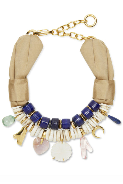 Thumbnail close-up of Lost In Paradise Necklace. Stranded in a sea of boring jewelry? We've designed your ultimate desert-island accessory, a one-of-a-kind necklace of deep blue Tibetan glass and conch shell beads. Featuring a trove of charms in mother-of-pearl, lapis and gold-plated coral charms, with an elegant taupe raw silk shantung closure.