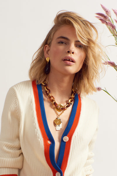 Thumbnail of model wearing Elba Necklace. We're feeling some major layering love for the oversized gold and tortoise link necklace with assorted shell, enamel, and angelite charms. The two strands are detachable and can be be worn individually or together.