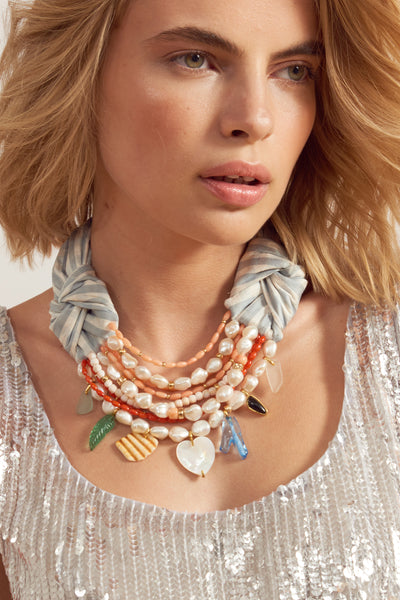 Thumbnail of model wearing Breton Beach Necklace. Lizzie's latest creation combines her most joyful mix of color and material with a timeless sophistication. The light blue & white gingham silk shantung necklace is an absolute jaw-dropper, with multi-strand freshwater pearl and coral beads as well as a unique array of charms.