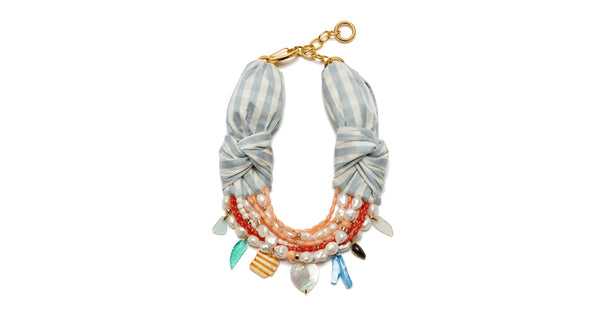 Full view of Breton Beach Necklace. Lizzie's latest creation combines her most joyful mix of color and material with a timeless sophistication. The light blue & white gingham silk shantung necklace is an absolute jaw-dropper, with multi-strand freshwater pearl and coral beads as well as a unique array of charms.