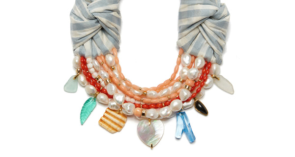 Close-up of charms and beads on Breton Beach Necklace. Lizzie's latest creation combines her most joyful mix of color and material with a timeless sophistication. The light blue & white gingham silk shantung necklace is an absolute jaw-dropper, with multi-strand freshwater pearl and coral beads as well as a unique array of charms.