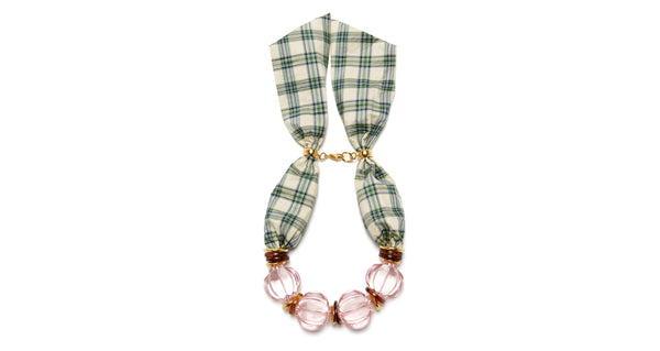 Full view of Riviera Necklace. Preppy, pretty and perfect for transforming your outfit,  the light pink fluted acrylic and gold-plated bead necklace is uniquely capped off with an adjustable green & ivory plaid silk taffeta closure. Looks fantastic with a white t-shirt or silk blouse.