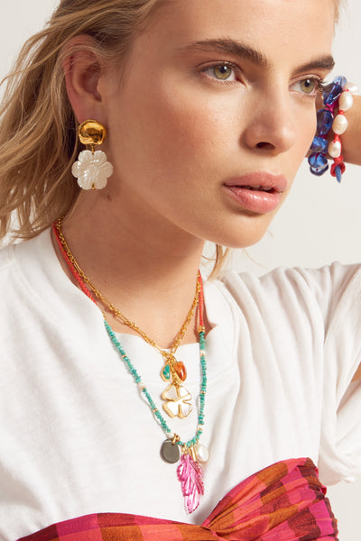 Thumbnail of model wearing Neon Reef Charm Necklace. We love this charm necklace for its playful, beachy vibe and how it surfs the wave between bold and delicate. Beaded with turquoise chips and braided with coral-colored adjustable cord, the Neon Reef features natural stone, hot pink quartz leaf, red-enameled and gold-plated amulet and freshwater pearl charms.
