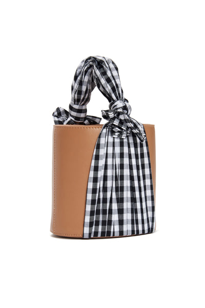 Thumbnail side-view of Florent Bucket Bag In Park. City picnic, anyone? This one-of-a-kind tan leather bucket bag means business, while the winsome silk gingham fabric begs to play hookey on a spring afternoon. We think it's an unexpected match made in heaven.