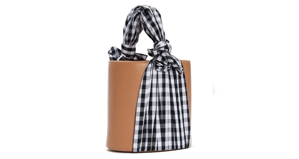 Side view of Florent Bucket Bag In Park. City picnic, anyone? This one-of-a-kind tan leather bucket bag means business, while the winsome silk gingham fabric begs to play hookey on a spring afternoon. We think it's an unexpected match made in heaven.