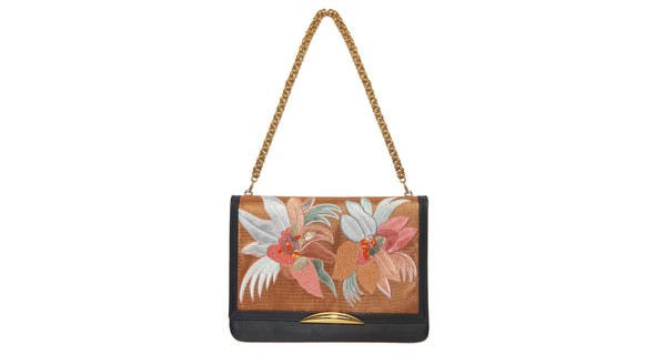 Full view of Port Of Call Clutch In Tropical Canopy. Wanted: a bold and sophisticated trend-setter to flaunt this one-of-a-kind purse. Black leather fold-over clutch with textured floral embroidery, architectural gold-plated hardware and detachable chain strap.