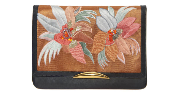 Close-up view of Port Of Call Clutch In Tropical Canopy. Wanted: a bold and sophisticated trend-setter to flaunt this one-of-a-kind purse. Black leather fold-over clutch with textured floral embroidery, architectural gold-plated hardware and detachable chain strap.