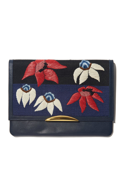 Thumbnail of Port Of Call Clutch In Garden's Edge. Wanted: a bold and sophisticated trend-setter to flaunt this one-of-a-kind purse. Black leather fold-over clutch with textured navy, red and white floral embroidery, architectural gold-plated hardware and detachable chain strap.