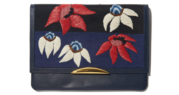 Full view of Port Of Call Clutch In Garden's Edge. Wanted: a bold and sophisticated trend-setter to flaunt this one-of-a-kind purse. Black leather fold-over clutch with textured navy, red and white floral embroidery, architectural gold-plated hardware and detachable chain strap.