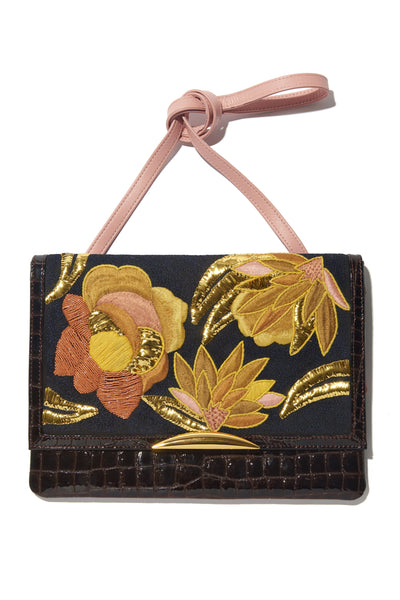 Thumbnail of Port Of Call Clutch In Sunrise Flora. We can't believe we made only one of these bags -- the sumptuous detailing and rich color palette are truly to die for. One-of-a-kind chocolate patent leather fold-over clutch with textured floral embroidery, architectural gold-plated hardware and pink leather strap.