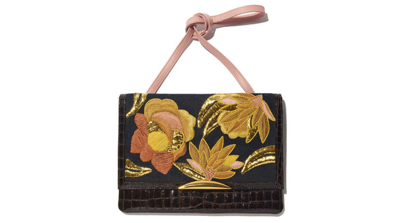 Full view of Port Of Call Clutch In Sunrise Flora. We can't believe we made only one of these bags -- the sumptuous detailing and rich color palette are truly to die for. One-of-a-kind chocolate patent leather fold-over clutch with textured floral embroidery, architectural gold-plated hardware and pink leather strap.