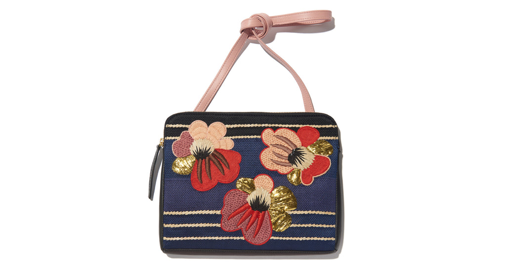 Full view of Safari Clutch In Blooming Poppy. Take me home tonight: one-of-a-kind statement purse seeks bold style maven. This black leather zipper clutch features a red and pink embroidered floral motif and detachable pink leather strap. Good times guaranteed.