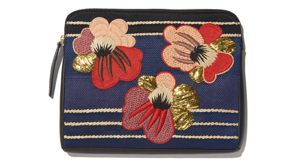 Close-up view of Safari Clutch In Blooming Poppy. Take me home tonight: one-of-a-kind statement purse seeks bold style maven. This black leather zipper clutch features a red and pink embroidered floral motif and detachable pink leather strap. Good times guaranteed.