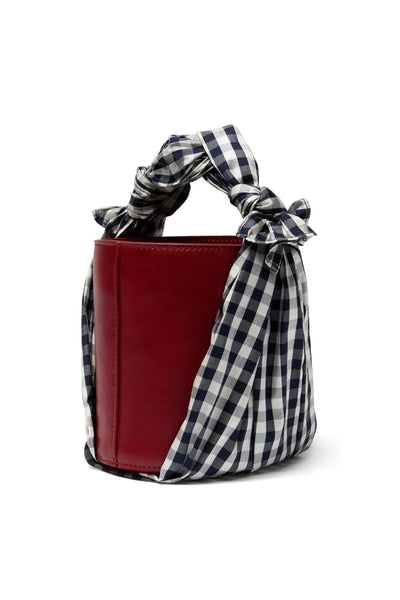 Side view thumbnail of Florent Bucket Bag In Picnic. The dark rust leather bucket bag means business, while the winsome silk gingham fabric begs to play hookey on a spring afternoon. We think it's an unexpected match made in heaven.