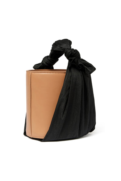 Thumbnail side view of Florent Bucket Bag In Midnight. Our newest purse silhouette projects elegant minimalism through an unexpected pairing of materials. The camel-colored leather bucket bag is wrapped with raw black silk fabric, for an effect that's both understated and eye-catching.