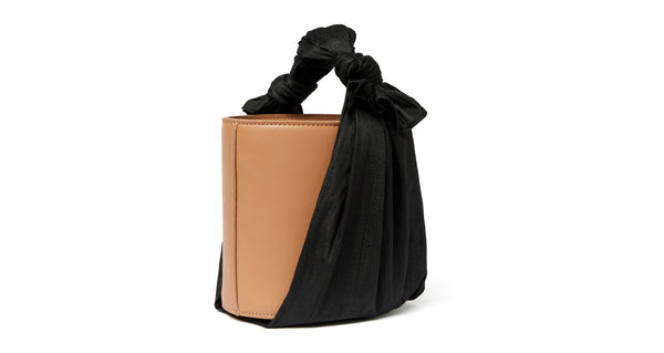 Full side view of Florent Bucket Bag In Midnight. Our newest purse silhouette projects elegant minimalism through an unexpected pairing of materials. The camel-colored leather bucket bag is wrapped with raw black silk fabric, for an effect that's both understated and eye-catching.