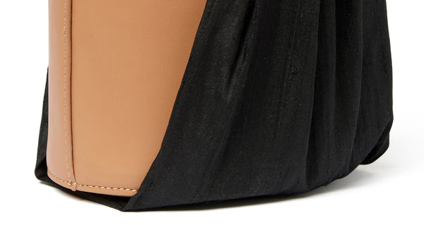 Bottom detail of Florent Bucket Bag In Midnight. Our newest purse silhouette projects elegant minimalism through an unexpected pairing of materials. The camel-colored leather bucket bag is wrapped with raw black silk fabric, for an effect that's both understated and eye-catching.