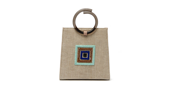 Full back view of Pronto Purse In Set Sail. High-quality and distinctively stylish, we predict the Pronto mini bag in taupe linen and leather will become your go-to accessory to elevate every outfit. With multicolored embroidered concentric square motif and smoky gray acrylic top-handles.