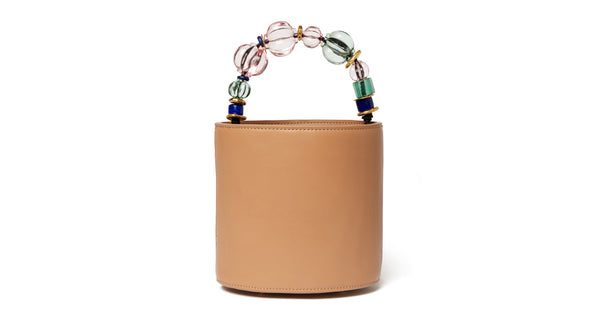 Full view of Florent Bucket Bag In Riviera. Play it from the top! The classic camel leather bucket bag gets a truly delightful update with a multicolored acrylic, gold-plated, and glass bead top-handle.