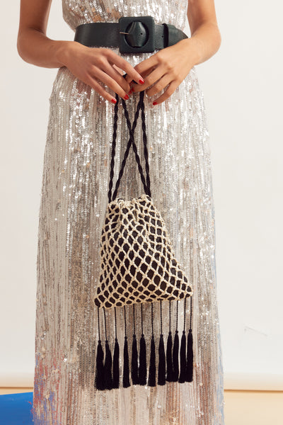 Thumbnail of model carrying Gala Wristlet In Fisherman's Net. It's easy to see why the Gala is our most popular new clutch style; this cream cord macrame drawstring purse is just bursting with drama and whimsy.  With amazing black tassel fringe and twist cord wristlet.