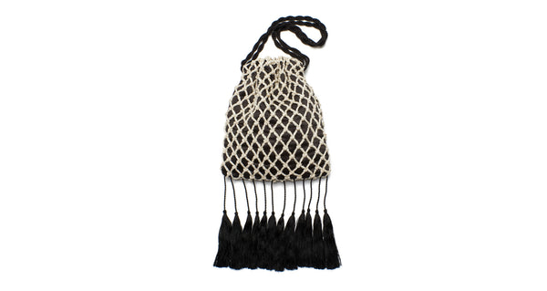 Full view of Gala Wristlet In Fisherman's Net. It's easy to see why the Gala is our most popular new clutch style; this cream cord macrame drawstring purse is just bursting with drama and whimsy.  With amazing black tassel fringe and twist cord wristlet.