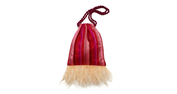 Full view of Gala Wristlet In Flamingo Stripe. Real talk: it doesn't get much more fun than this. Strut your stuff in the pink and red drawstring purse with delicate bead embroidery, light pink ostrich feather fringe, and magenta twist cord wristlet.