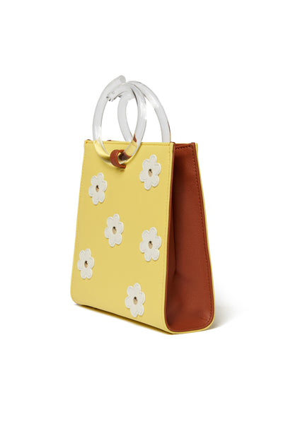 Thumbnail side view of Pronto Purse In Daisy Field. You can't help but feel sunny with this butter yellow leather mini bag on your arm. The Pronto purse's retro charm is enhanced with studded white leather daisies and clear acrylic handles.