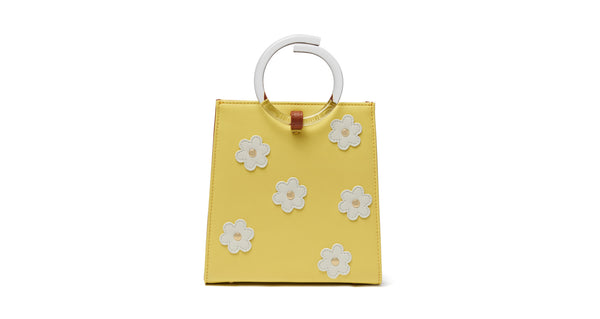 Full view of Pronto Purse In Daisy Field. You can't help but feel sunny with this butter yellow leather mini bag on your arm. The Pronto purse's retro charm is enhanced with studded white leather daisies and clear acrylic handles.