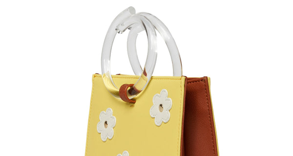 Side view top detail of Pronto Purse In Daisy Field. You can't help but feel sunny with this butter yellow leather mini bag on your arm. The Pronto purse's retro charm is enhanced with studded white leather daisies and clear acrylic handles.