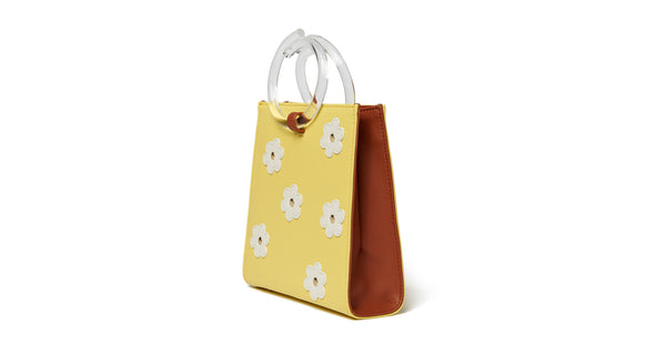 Side view of Pronto Purse In Daisy Field. You can't help but feel sunny with this butter yellow leather mini bag on your arm. The Pronto purse's retro charm is enhanced with studded white leather daisies and clear acrylic handles.