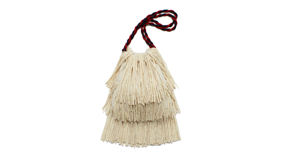 Full view of Gala Wristlet In Puka Fringe. It's easy to see why the Gala is our most popular new clutch style; this hand-sewn shell fringe drawstring purse is an eye-catching stunner. With navy and red twist cord wristlet.